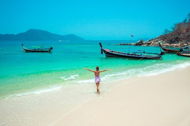 Os braços de mulher feliz viajante abrem vestido relaxante e olhando para a paisagem bela natureza com barcos tradicionais de cauda longa. praia do mar turístico tailândia, ásia, viagem de férias de férias de verão - Foto Premium
