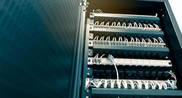 Os cabos ethernet da rede se conectam para alternar o rack do servidor no hub do centro de dados da universidade Foto Premium