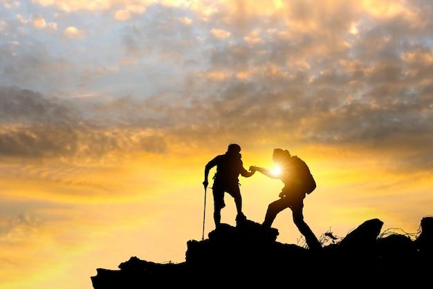 Os caminhantes masculinos e fêmeas que escalam acima o penhasco da montanha e um deles que dão a mão amiga. Foto Premium