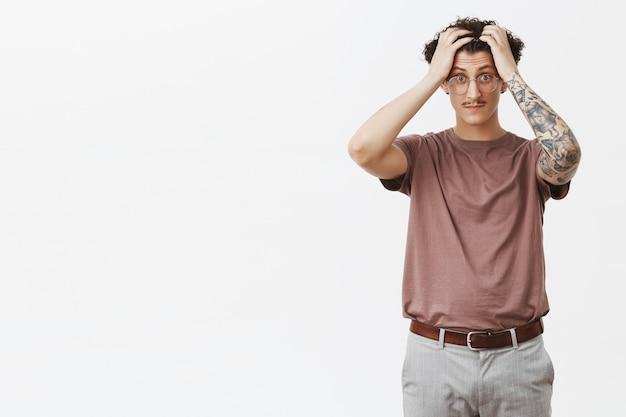 Os cérebros fervem de alunos estúpidos. retrato de um jovem atraente de cabelos encaracolados, em choque e em choque, com bigode engraçado e tatuagens tocando o cabelo, olhos esbugalhados, parecendo pressionado e estressado Foto gratuita