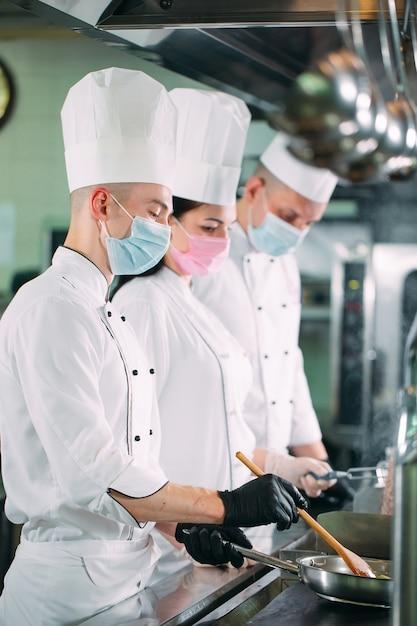 Os chefs em luvas e máscaras protetoras preparam os alimentos na cozinha de um restaurante ou hotel. Foto Premium