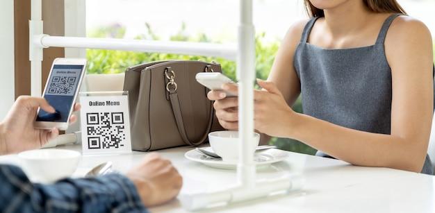 Os clientes asiáticos do panorama digitalizam o menu online do código qr. os clientes sentaram-se na mesa de distanciamento social para um novo estilo de vida normal no restaurante Foto Premium