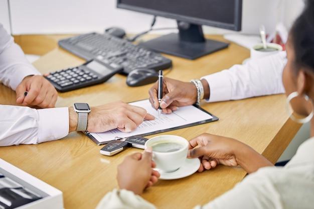 Os clientes bebem uma xícara de café e têm uma conversa amigável com a concessionária Foto Premium