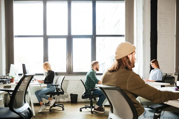 Os colegas trabalham no escritório usando computadores. olhando de lado. Foto gratuita
