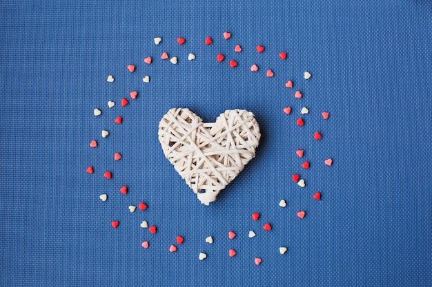 Os corações brancos em um azul são cercados por doces coloridos. Foto Premium