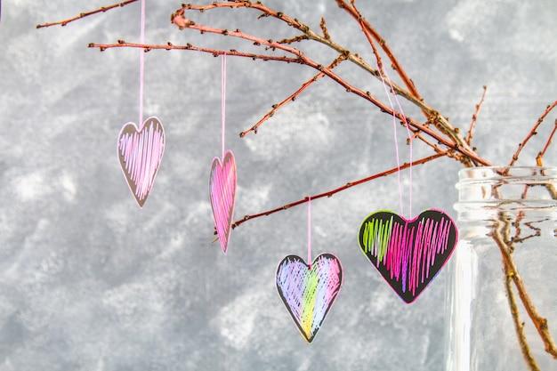 Os corações preto-cor-de-rosa penduram em ramos em um fundo concreto cinzento. o conceito de dia dos namorados. Foto Premium