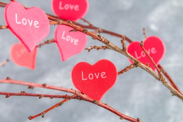 Os corações vermelhos amam o cair em ramos no fundo concreto. árvore de amor. Foto Premium