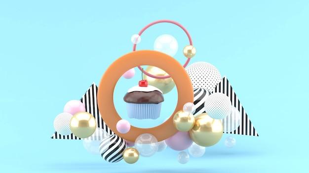 Os cupcakes estão no centro do círculo, entre as bolas coloridas no espaço azul Foto Premium
