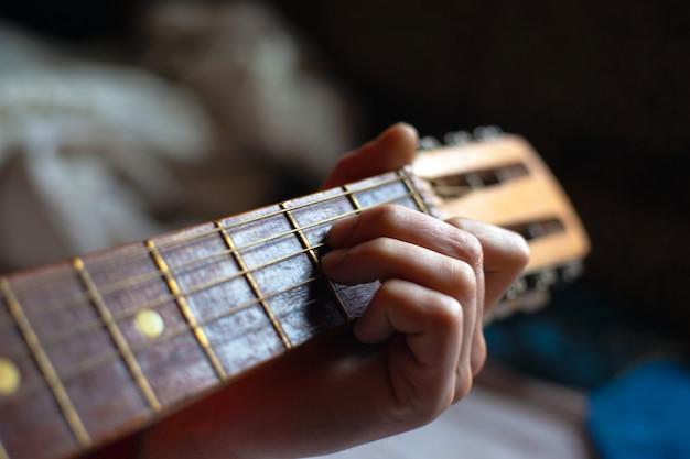 Os dedos seguram o violão acústico do braço da guitarra. Foto Premium
