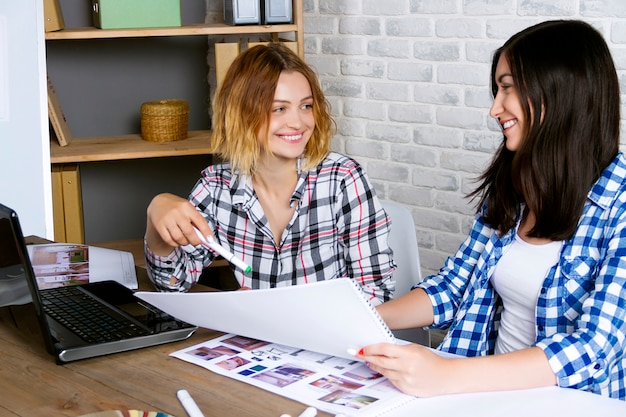 Os designers de interiores jovens freelancers trabalhando desenvolvem novo projeto de apartamento no estúdio de design. reunião feminina de duas mulheres garota com mesa de reunião com pin up esboços desenhos e rascunhos de novo projeto Foto Premium