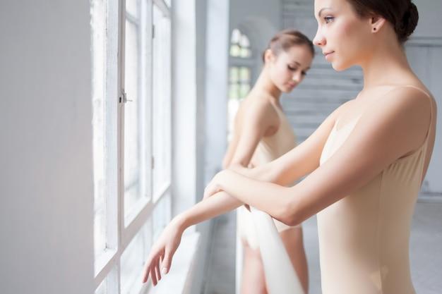 Os dois bailarinos clássicos posando no barre Foto gratuita