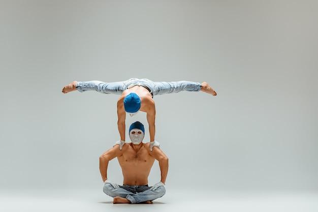 Os dois homens caucasianos acrobáticos de ginástica em pose de equilíbrio Foto gratuita