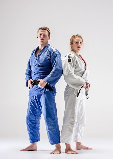 Os dois lutadores de judocas posando em cinza Foto gratuita