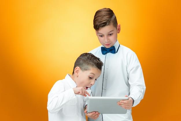 Os dois meninos usando laptop no espaço laranja Foto gratuita