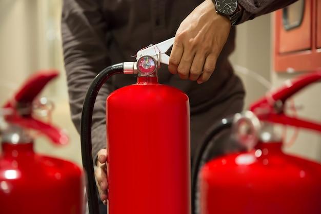 Os engenheiros de close-up estão apertando a alça no extintor de incêndio. Foto Premium