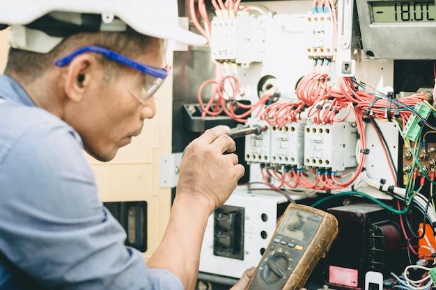 Os engenheiros estão verificando os circuitos elétricos dos sistemas de alimentação de contêineres refrigerados. Foto Premium