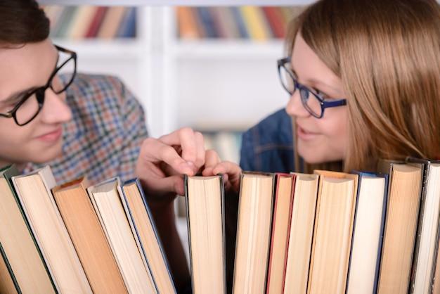 Os estudantes felizes olham o livro para ler na biblioteca. Foto Premium