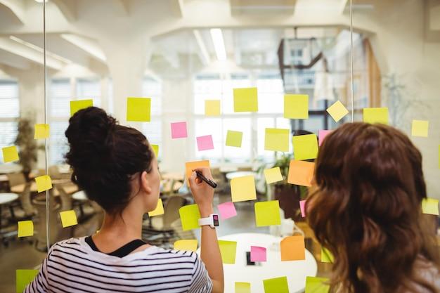 Os executivos de negócios escrevendo em notas pegajosas Foto gratuita