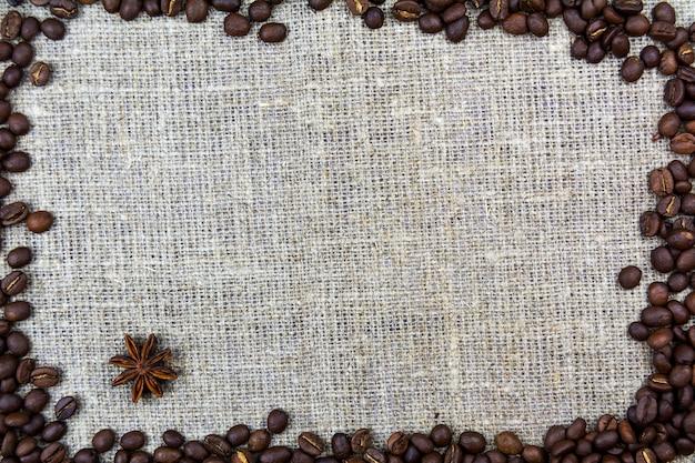 Os feijões de café encontram-se em uma serapilheira de pano de linho. fundo retrô Foto Premium