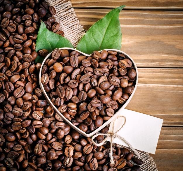 Os feijões de café fritados encontram-se sob a forma do coração em placas de madeira e na serapilheira. Foto Premium
