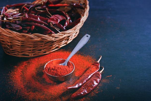 Os flocos de pimenta vermelha e o pó de pimentão estouraram no fundo preto Foto Premium
