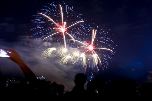 Os fogos-de-artifício coloridos na noite iluminam acima o céu com exposição do brilho. Foto Premium