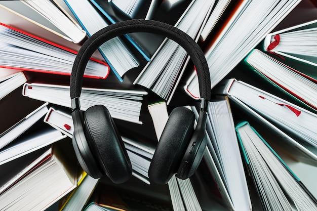 Os fones de ouvido pretos sem fio estão nos livros. o conceito de aprendizagem através de um audiolivro. para ouvir o livro. Foto Premium
