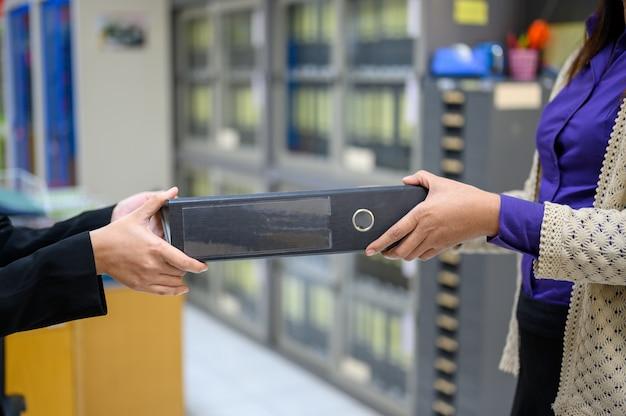 Os funcionários usam documentos pretos móveis no escritório Foto Premium