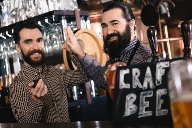 Os garçons de homens barbudos dão cinco no bar de cervejas artesanais. Foto Premium