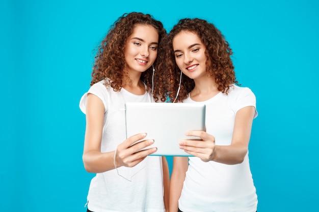 Os gêmeos de duas mulheres que olham a tabuleta, sorrindo sobre o azul. Foto gratuita
