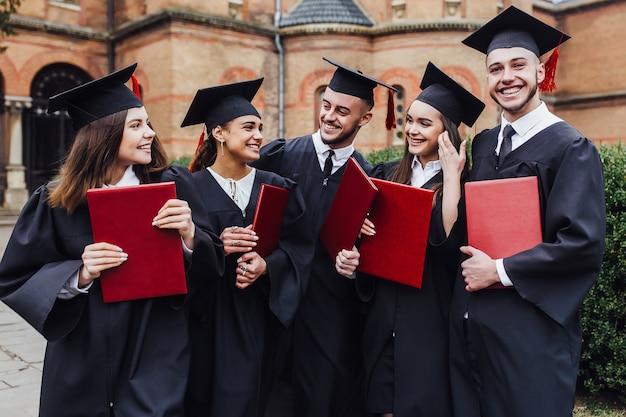Os graduados abraçam, apreciam e olham para a câmera na cerimônia de formatura Foto Premium