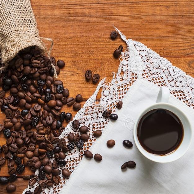 Os grãos de café derramaram perto da xícara Foto gratuita
