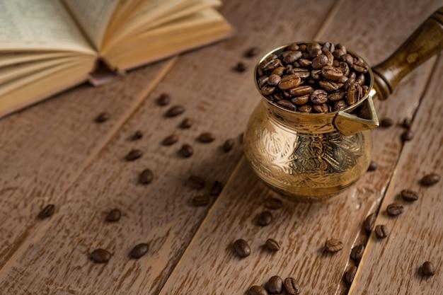 Os grãos de café torrados frescos no cezve abriram o livro e o copo na mesa de madeira. Foto Premium
