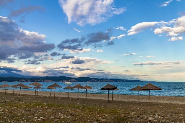 Os guarda-chuvas de praia da palha na costa vazia do mar negro na abkhásia, pitsunda no por do sol. praia de calhau, montanhas, mar, céu com nuvens Foto Premium