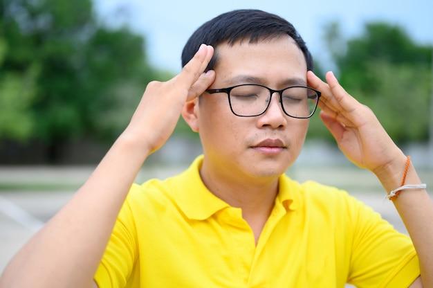 Os homens asiáticos usam camisas amarelas com estresse, cansaço visual. Foto Premium