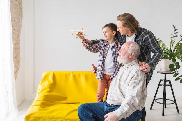 Os homens da família de diferentes gerações estão segurando o avião modelo Foto gratuita