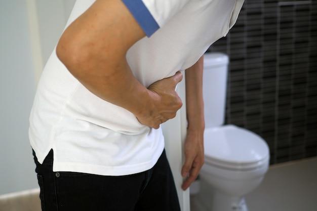 Os homens têm dor abdominal. quer cagar. conceito de diarréia Foto Premium