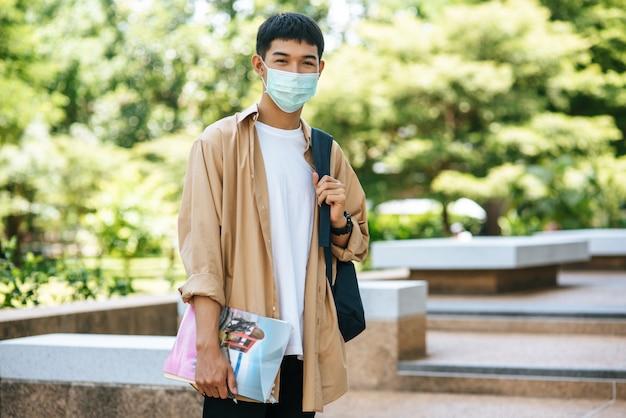 Os homens usam máscaras, carregam livros e carregam uma mochila nas escadas. Foto gratuita