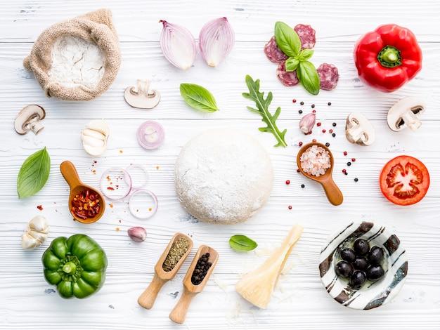 Os ingredientes para pizza caseira em fundo branco de madeira. Foto Premium
