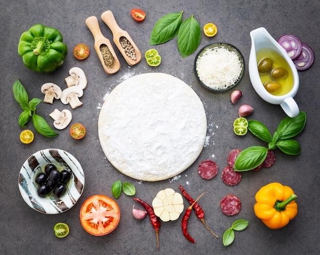 Os ingredientes para pizza caseira em fundo escuro de pedra. Foto Premium