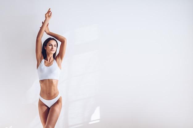 Os jovens couberam a mulher na roupa interior branca na parede branca isolada. mulher atraente magro muscular com barriga lisa. copie o espaço para texto. cuidados com o corpo, vida saudável e esportiva, depilação, conceito de ioga Foto Premium