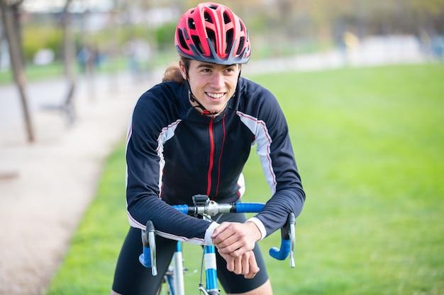 Os jovens de sorriso cabem o ciclista masculino no sportswear e capacete sentado na bicicleta no parque e olhando para a câmera Foto Premium