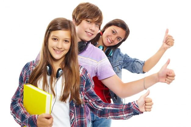 Os jovens, em linha com polegares acima Foto gratuita