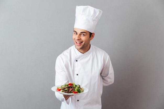 Os jovens felizes cozinham na salada guardando uniforme. Foto gratuita
