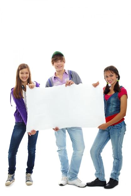 Os jovens felizes que prendem um sinal em branco Foto gratuita