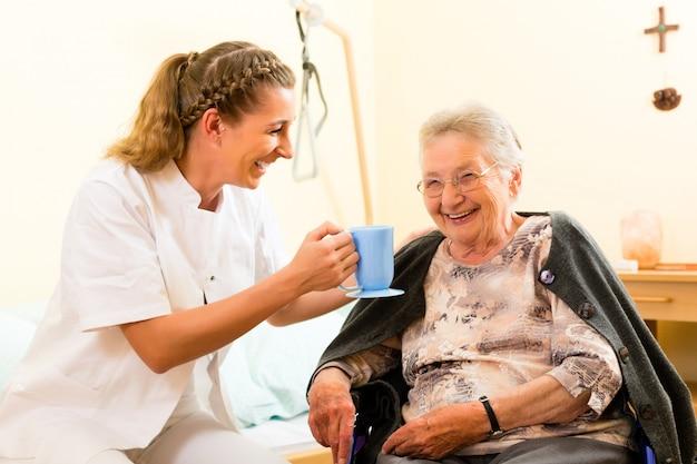 Os jovens nutrem e fêmea sênior no lar de idosos Foto Premium