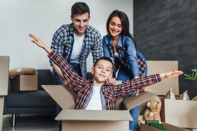 Os jovens se divertem enquanto se mudam para um novo apartamento. os pais empurram a caixa com o filho e brincam com ele Foto Premium