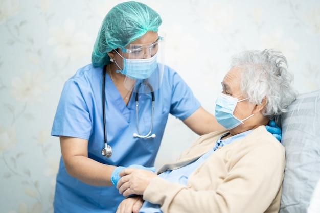 Os médicos asiáticos que usam protetor facial e epi se adaptam ao novo normal para verificar a proteção do paciente ao covid-19 coronavírus. Foto Premium