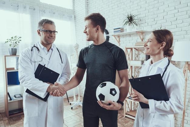 Os médicos estão falando com o jogador de futebol. Foto Premium