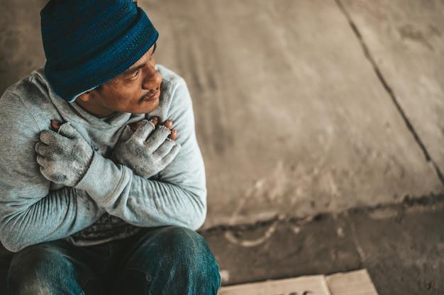 Os mendigos sentam-se debaixo da ponte com uma mensagem de sem-teto. por favor ajude. Foto gratuita